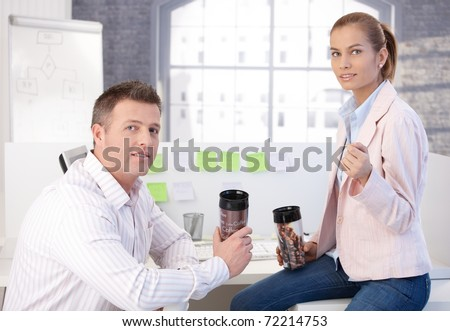 Colleagues during coffee break in office, chatting drinking coffee.?