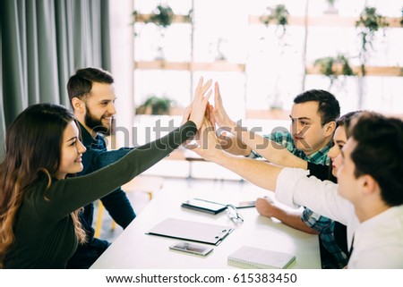 Colleagues giving high-five in meeting room at creative office room #615383450
