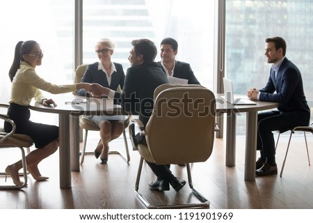 Colleagues handshake getting acquainted during company meeting in office, business partners shake hands introducing at negotiation, businessman congratulate female employee with promotion #1191901969