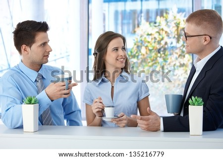 Colleagues on coffee break in business office, talking and smiling.