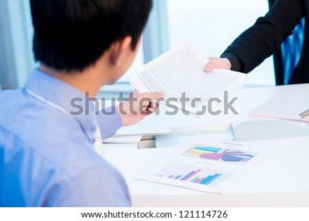Colleagues passing a business document to each other
