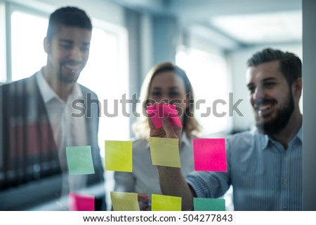 Colleagues using sticky notes for their business schedule. #504277843