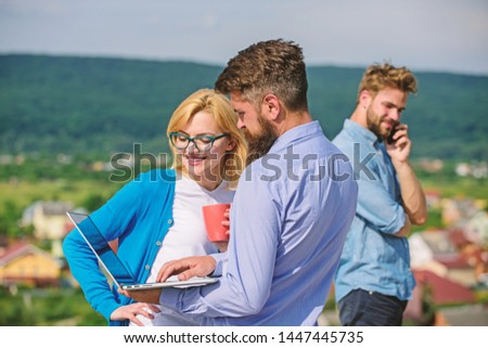 Colleagues with laptop work outdoor sunny day, nature background. Coffee break concept. Colleagues pay attention screen laptop while man talking phone. Business partners meeting non formal atmosphere. #1447445735
