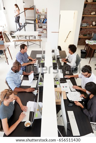 Colleagues working at a busy open plan office, vertical