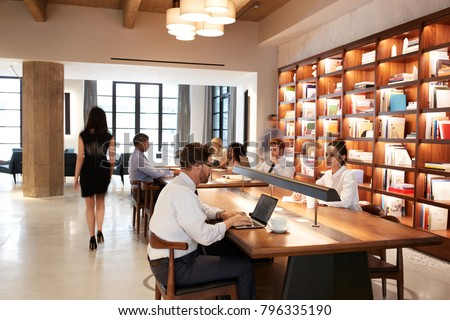 Colleagues working at desks in a busy open plan office area