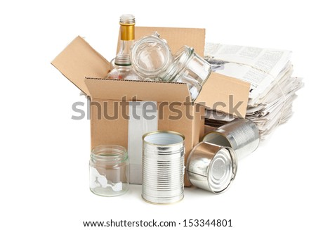 Collected glass bottles, tin cans and newspaper in carton box for recycling on white background