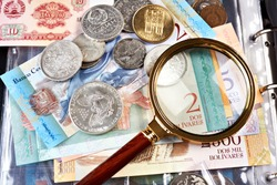 Collecting old coins and banknotes. Numismatics. Old money and notes with magnifying glass