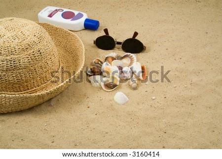 Collecting Shells on the Beach.  Seashells, Straw Hat, Sun Glasses, Sun Block on a Sandy Beach