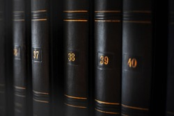 Collection of a multi-volume old encyclopedia in a dark, worn cover with yellowish numbers. Books with knowledge and information. Learning.