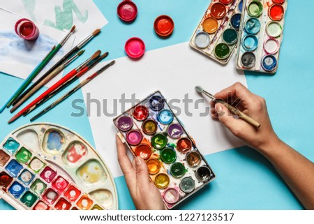 collection of accessories for artists. Canvas, oil paint tube, artistic brushes, palette, and hand with a brush lying on a blue table. Artist master background. Flat lay top view. #1227123517
