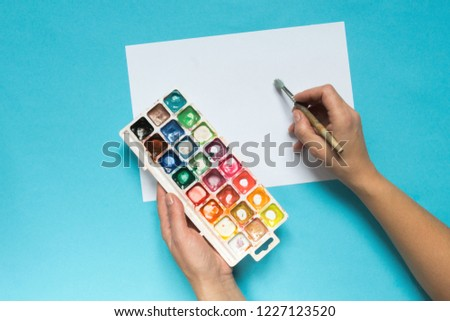 collection of accessories for artists. Canvas, oil paint tube, artistic brushes, palette, and hand with a brush lying on a blue table. Artist master background. Flat lay top view. #1227123520