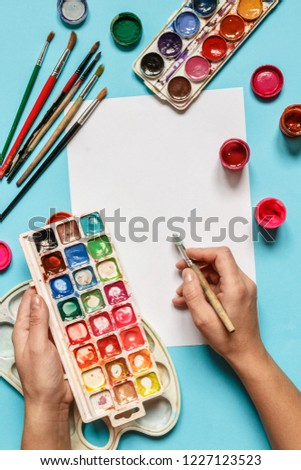 collection of accessories for artists. Canvas, oil paint tube, artistic brushes, palette, and hand with a brush lying on a blue table. Artist master background. Flat lay top view. #1227123523