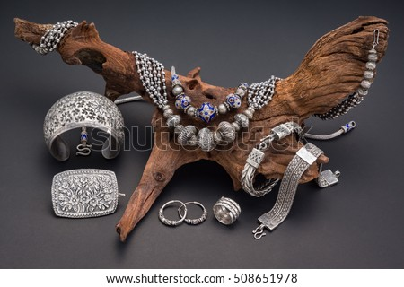 Collection of antique traditional silver jewelry on old wood and black paper