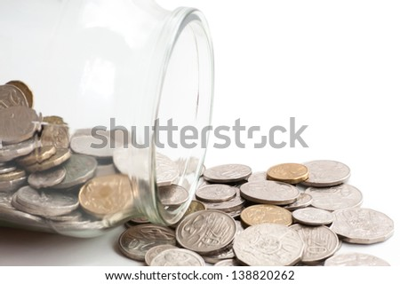 Collection of Australian coins spilling out of a glass jar tipped on its side