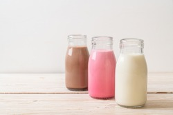 Collection of beverage chocolate milk, pink milk and fresh milk in bottle on wood table