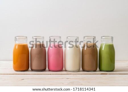 Collection of beverage Thai milk tea, matcha green tea latte, coffee, chocolate milk, pink milk and fresh milk in bottle on wood table