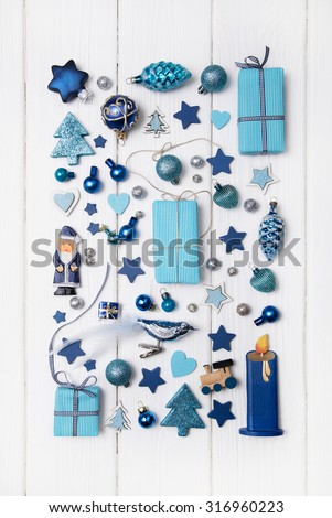 Collection of blue and turquoise miniatures with presents for christmas decoration on wooden white background.