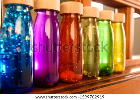 Collection of bottles of calm, plastic with wooden stopper, toy filled with liquids and materials of bright colors and glitter to relax children when they are nervous.