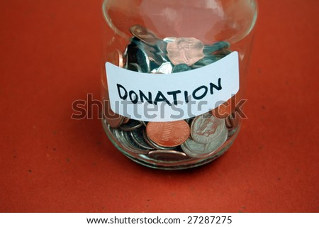 Collection of coins in a jar labeled for donation - stock photo