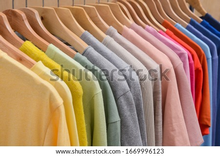 collection of colorful row t-shirts with sweatshirt ,sweater hanging on hangers on a white background    Foto stock ©