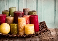 collection of decorative candles on a rustic antique wooden background