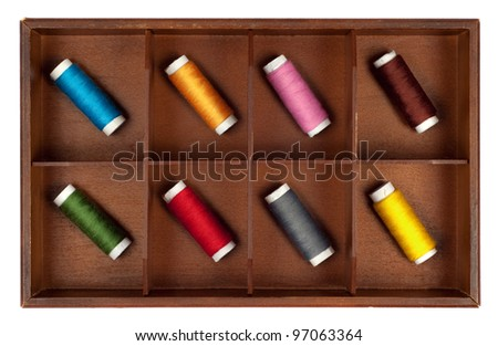 Collection of different color spools of thread  arranged in a grunge wooden box.Isolated on white background