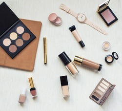 Collection of different professional make up products on textile background top view. Make up set studio shot.Woman fashion accessories. Autumn nude brown and beige mood