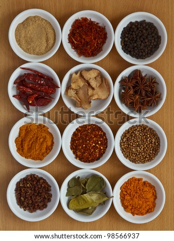 Collection of different spices and herbs on wooden board