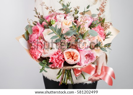 Collection of different varieties of garden roses, carnations and eucalyptus. Girl's hands holding gentle colors flowers bouquet on white background.