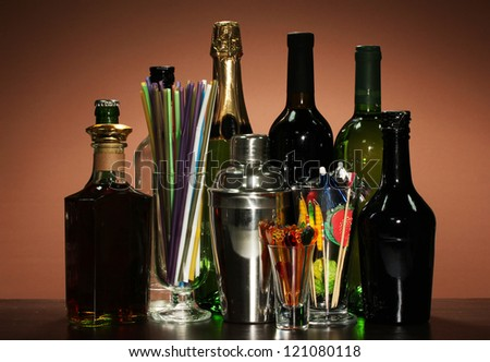 Collection of drinks, cocktail shaker and  other bartender equipment on color background