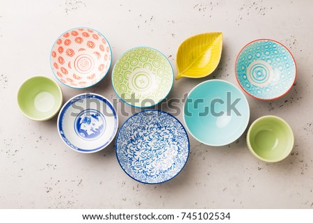 Collection of empty colorful (pastel) decorative ceramic bowls on grey stone background. Layout captured from above (top view, flat lay). #745102534