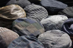 Collection of flat caps on display at a steam rally