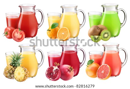 Collection of fresh juices in pitchers. Nearby are the ingredients of juices.