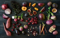 Collection of fresh purple toned vegetables and fruits on dark rustic distressed background, eggplant, turnip, mango, carrot, , radishes, kale, kidney beans, plum, passionfruit, cherries