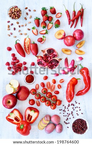 Collection of fresh red toned vegetables and fruits raw produce on white rustic background, peppers capsicum chilli strawberry raspberry pomegranate tomato paprika azuki beans plum