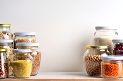 Collection of grain products in storage jars in pantry. Copyspace background.