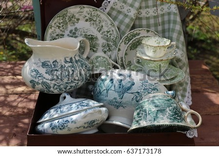Collection of green and white stamped dining and serving antique, vintage ironstone elegant cream colored dish: mug, cup, plate, pitcher, soup tureen, linen napkin in old retro on wooden grey chair