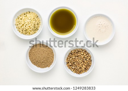 collection of hemp seed products: hearts, protein powder, milk and oil in small white bowls against white art canvas