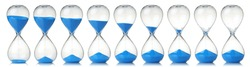 Collection of hourglasses with blue sand showing the passage of time