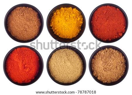 collection of indian spices (cumin, coriander, paprika, garam masala, curcuma, chili powder) on black ceramic cups isolated on white background