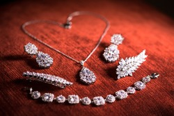 Collection of jewellery with diamond necklace and earrings on red velvet background
