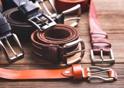 Collection of leather belts on a wooden table. Leather colored belts.