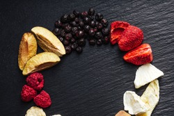 Collection of lyophilized freeze dried raspberries, bananas, apricots, plums, ananas, blueberries. Isolated close up on black slate board, plate, tray background.
