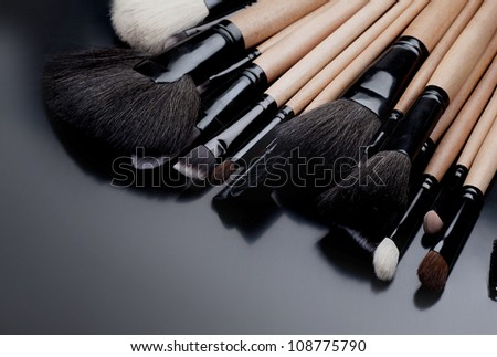 Collection of make-up brushes on black  background