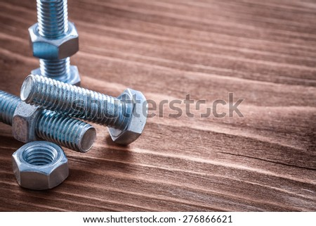 Collection of metal bolts and screw nuts on vintage wooden board construction concept