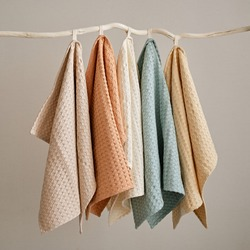 Collection of natural muslin kitchen towels are hung in a row on an unusual wooden hanger. Natural, soft, airy and stylish kitchen textiles.