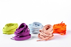 Collection of new colorful shoe laces. Composition of round multicolored strings for sport footwear over white background.