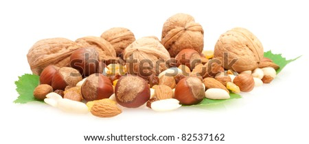 collection of nnuts and dried fruits on green leaves isolated on white background