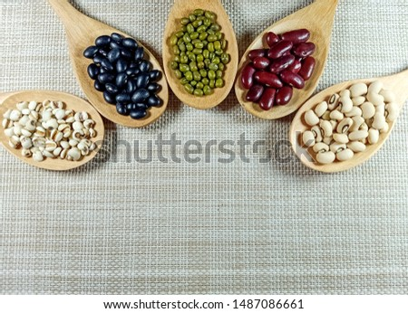 Collection of 5 nuts in a wooden spoon,Green beans, red beans, black beans, white beans, millet.