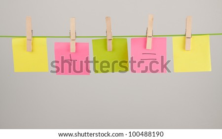 Collection of paper notes and clothes pegs on grey background